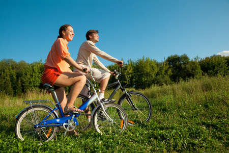 The girl and the man go for a drive on bicycles in a sunny day photo