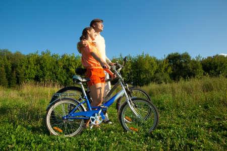 The girl and the man with bicycles embrace each other. photo