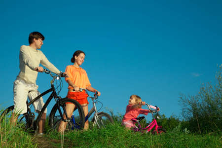 Family from three persons on bicycles. Parents look at a daughter. photo