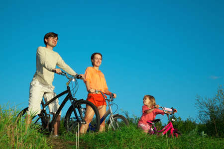 Parents with the daughter on bicycles, in the summer evening. photo