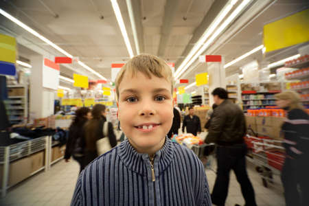 Smilling boy stand in centre of trading floor in supermarket photo