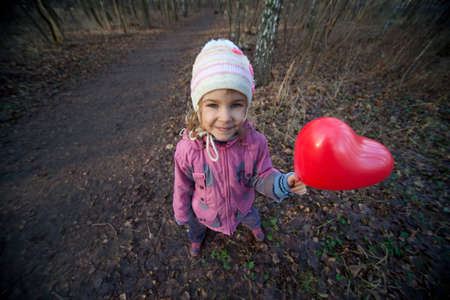 Small girl with inflatable red heart in terrible dark forest photo