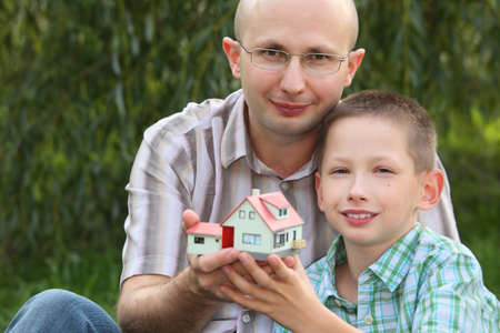 father and son keeping in their hands wendy house and looking at camera. focus on father's face. wendy house in out of focus. Stock Photo - 9111706