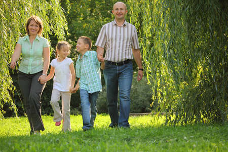 mom son: smiling family with two children. father, mother, son and daughter is walking in early fall park. Stock Photo