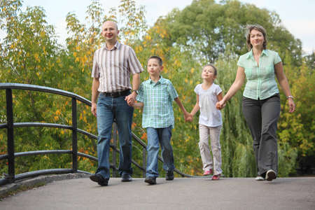 dad son: mom, dad, son and daughter is walking on bridge in early fall park. family is handies.
