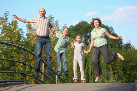 joyful family with two children is jumping on a bridge. family is handies. photo