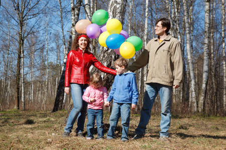 Parents with the daughter and the son walk in park with balloons. photo