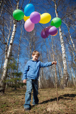 The boy with a sheaf of balloons in park in the spring photo