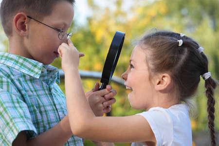 los niños en otoño parque. niño está examinando una niña alegre a través de Ampliador Foto de archivo - 9111640