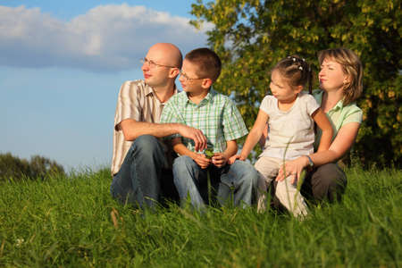 dad, mom, son and daughter in early fall park. they sitting on grass and looking at sunset photo