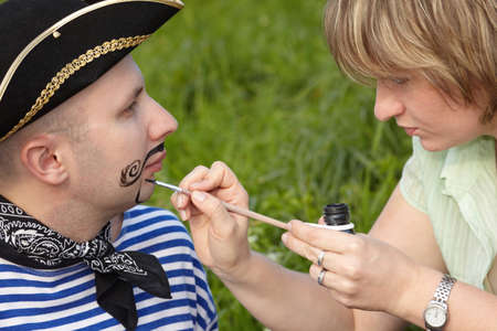 woman drawing funny whiskers and beard on man's face Stock Photo - 9113407