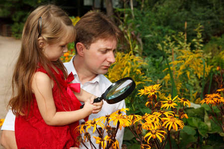 Little girl in red dress with father, considers plants through magnifying glass. photo