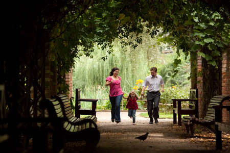pergola: Parents together with daughter run on tunnel from ivy in summer garden.