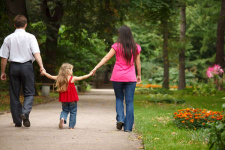 Parents together with daughter walk on summer garden. Leave afar keeping for hands. photo