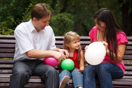 Parents together with daughter on bench in park in afternoon. In hands multi-coloured balloons. photo