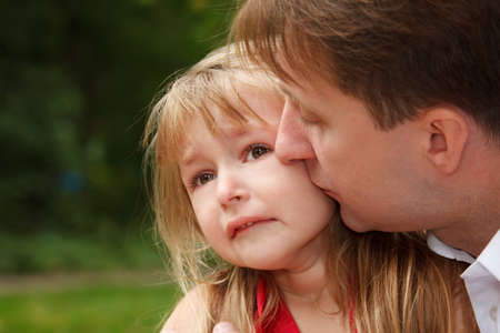sorrowfully: Sad little girl cries in park. Father calms her kissing on cheek.  Close up. Stock Photo