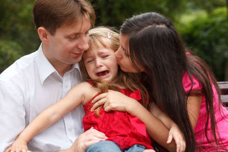 Parents calm crying girl on walk in summer garden. Girl sits in lap at father. photo