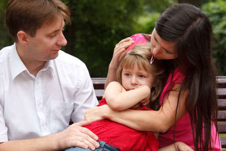 crying girl: Parents calm crying girl on walk in summer garden. Mum embraces daughter.
