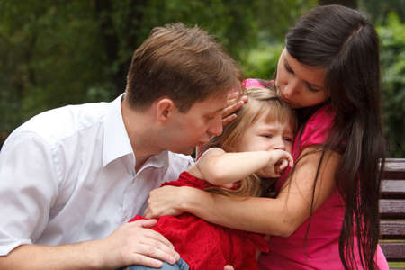 Parents calm crying girl on walk in summer garden. Mum embraces daughter. Close up. photo
