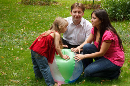 Parents together with little girl in summer garden. Play with big inflatable ball. Stock Photo - 9113510