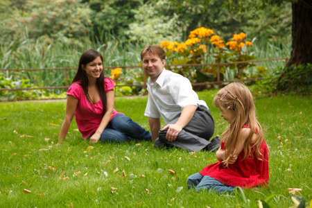 Parents together with little girl have rest in summer garden. Look at girl sitting on lawn. photo