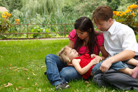 Parents together with little girl have rest in summer garden. Girl lies in lap parents. photo