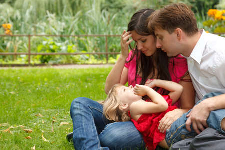 Parents together with little girl have rest in summer garden. Girl plays in lap parents. photo
