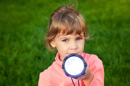 girl playing with lantern. Portrait of girl against a grass. grass background. girl looks in lens. girl shines a lantern in lens  photo