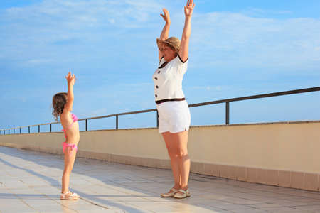 lifted hands: elderly woman and  little girl do morning exercise on veranda near seacoast, lifted hands upwards
