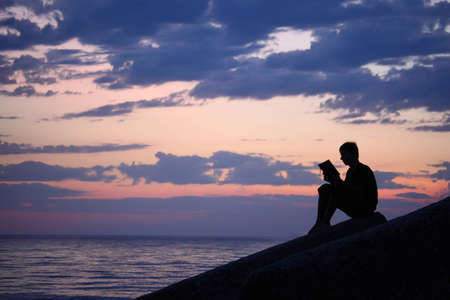 Silhouette guy sitting on breakwater in evening near sea, reads book photo
