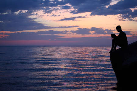 Silhouette guy sitting on breakwater in evening near sea, reads book, wide angle Stock Photo - 8982237