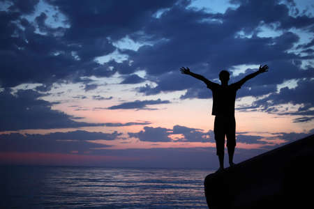strong boy: Silhouette guy placed hands in sides on breakwater in evening near sea Stock Photo