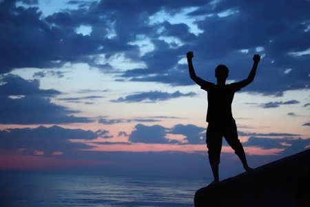Silhouette guy lifted hands upwards on breakwater in evening near sea photo