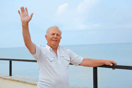 hand lifted: smiling senior on veranda near seacoast, lifted hand upwards