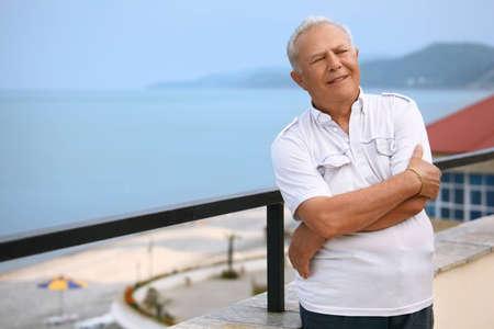 seacoast: smiling senior on veranda near seacoast
