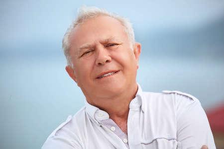 inclined: smiling senior near seacoast, inclined head aside