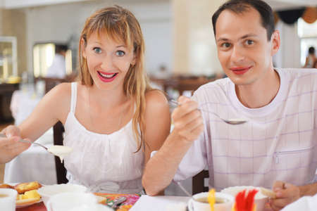 Married couple having breakfast at restaurant, eating cream wheat photo