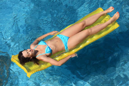 beautiful sexual woman relaxing on an inflatable mattress in pool photo