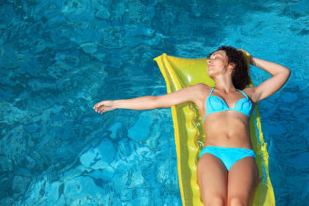 beautiful sexual woman relaxing on an inflatable mattress in pool, �as taken hand aside photo