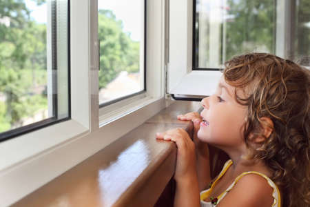 balcony window: pretty smiling little girl on balcony, look from window Stock Photo