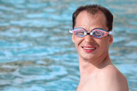 watersport: smiling young man in watersport goggles swimming in pool