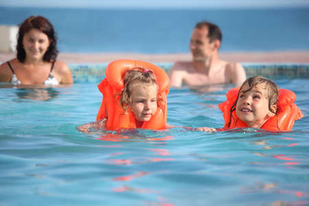 safety jacket: two little girls bathing in life jackets with parents in pool on a resort Stock Photo