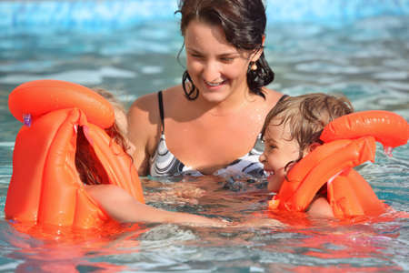two little girls bathing in lifejackets with young woman in pool on resort, Looking against each other photo
