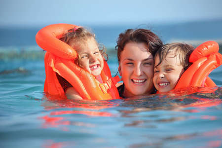 two little girls bathing in lifejackets with young woman in pool on resort photo