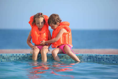 wet suit: two little girls in lifejackets sitting on ledge pool on resort Stock Photo
