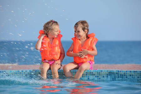 two little girls in lifejackets sitting on ledge pool on resort, Looking against each other photo