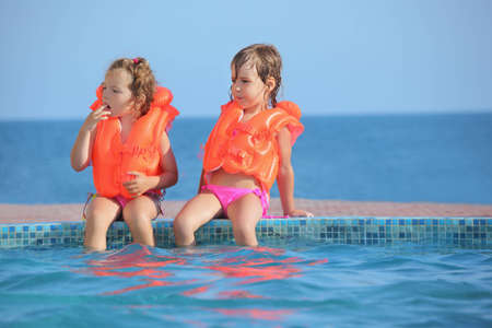 safety jacket: two little girls in lifejackets sitting on ledge pool on resort, Looking afar Stock Photo