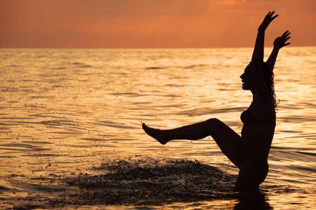Silhouette beautiful woman play in sea in evening photo