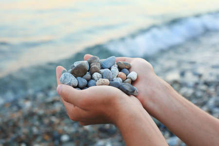 Handful of stones in hands, Against stones and sea  photo