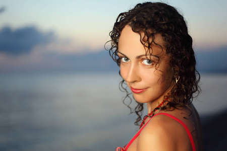 Curly beautiful young woman near sea in evening, Steadfastly looking photo
